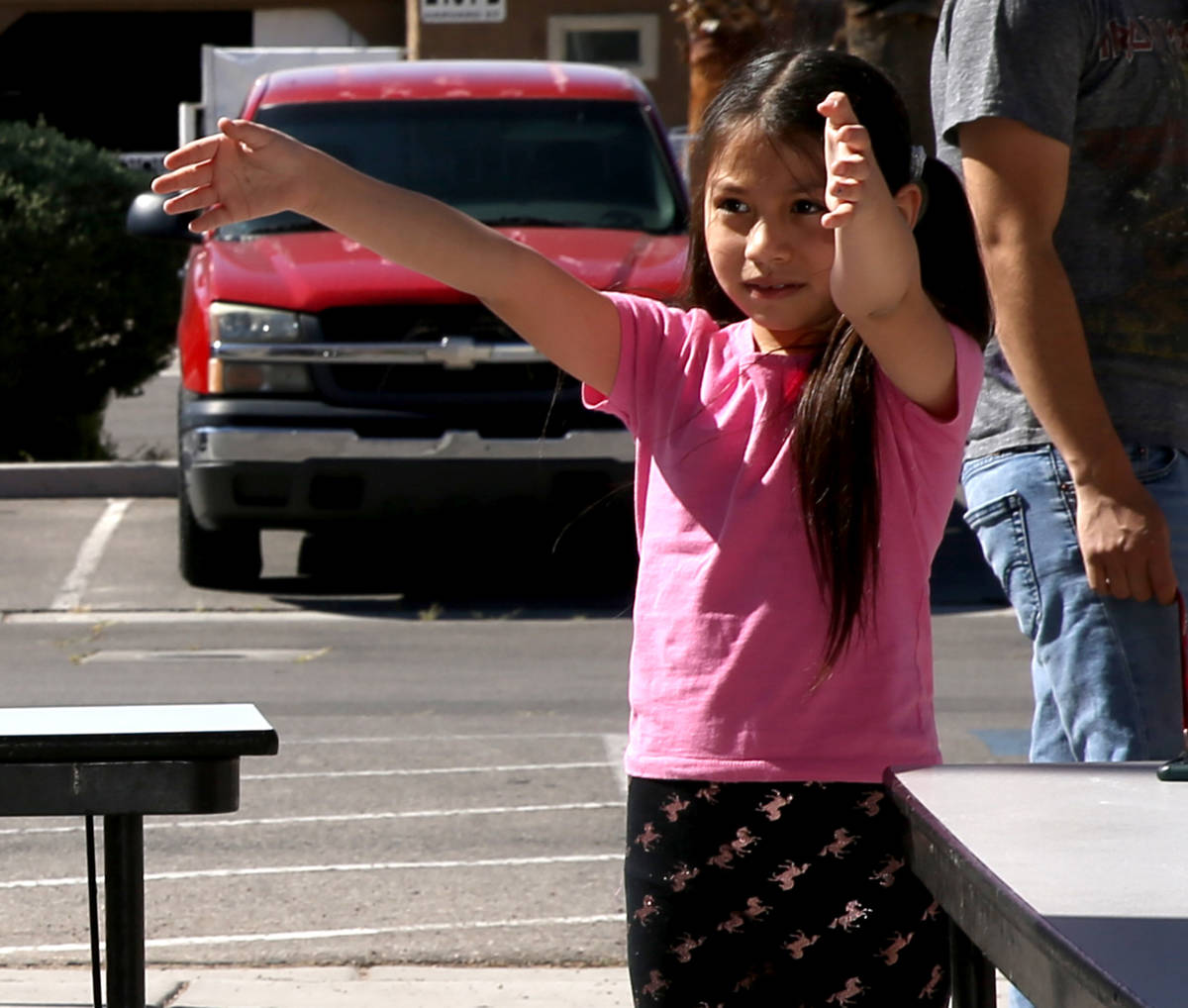 Emely Carreon, 7, a second grader at Martinez Elementary, gives her teacher-librarian Nichole B ...