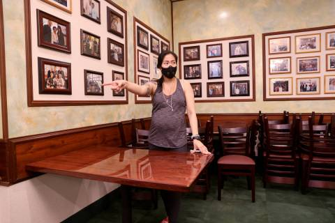 Penny Chutima, whose family owns Lotus of Siam, arranges tables six feet apart at the Las Vegas ...