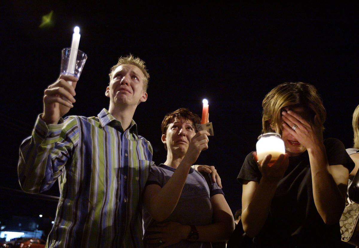 From left, Brad Barnes, Andrea Deashiell and Elizabeth Auten cry as they hold candles during a ...
