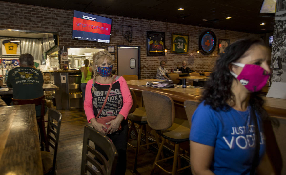 Customers Sandi Olson, left, and Terry Armstrong enter the dining area at Johnny Mac's Sports B ...