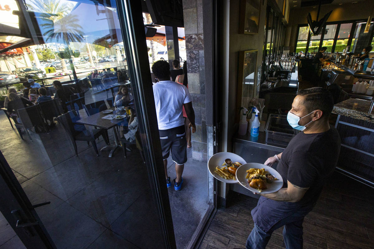 Rosendo Rodriguez brings food to patrons at Kona Grill in Boca Park as some restaurants open fo ...