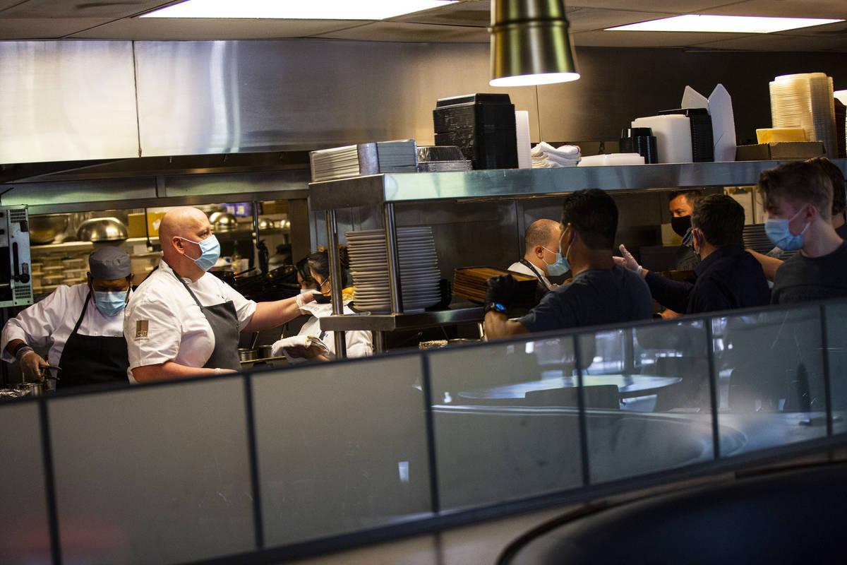Matt Hurley, executive chef of CUT by Wolfgang Puck, left, prepares food at Wolfgang Puck Playe ...