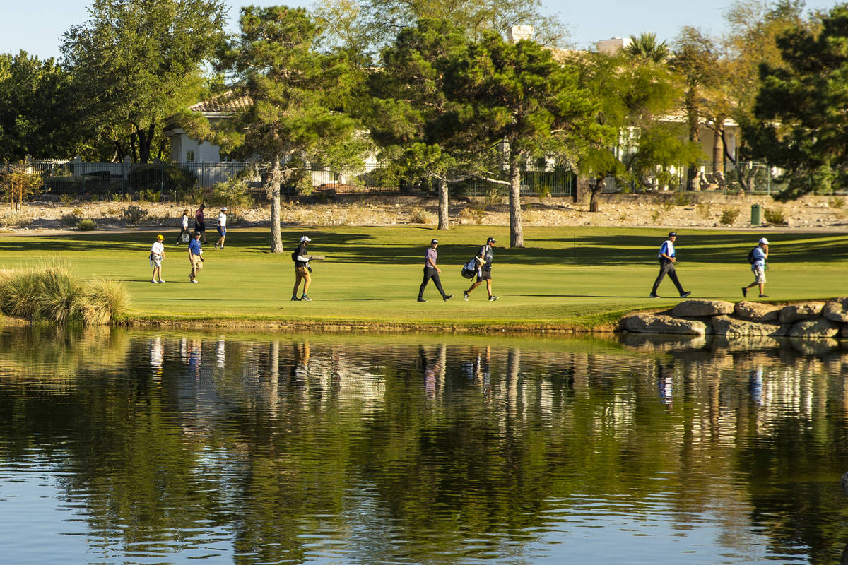 Golfers make their way up the fairway at hole 16 past a water feature during the third round of ...