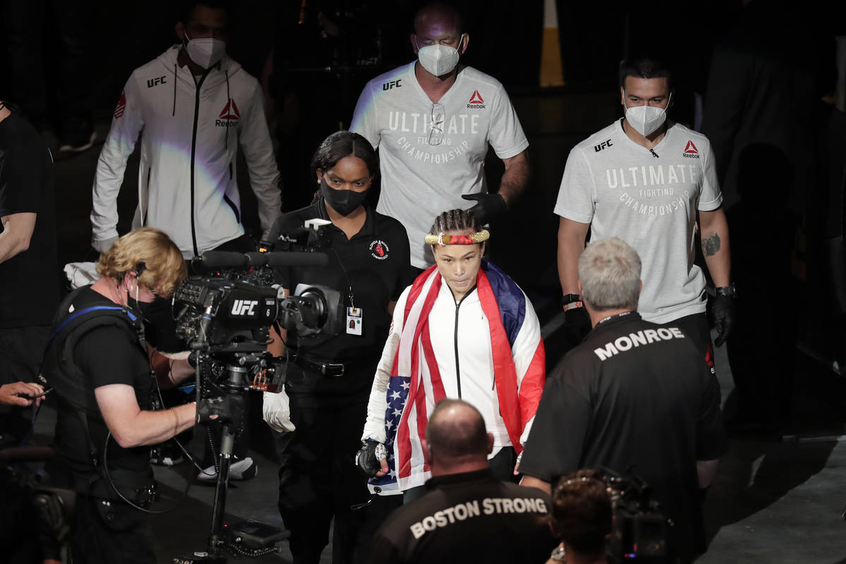 Michelle Waterson, center, enters the arena before her fight against Carla Esparaza at a UFC 24 ...