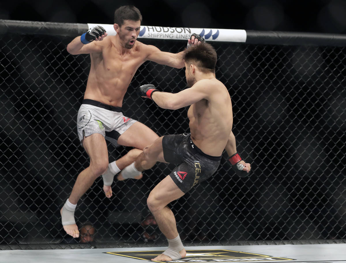 Dominick Cruz, left, tries to dodge a kick from opponent Henry Cejudo during a UFC 249 mixed ma ...