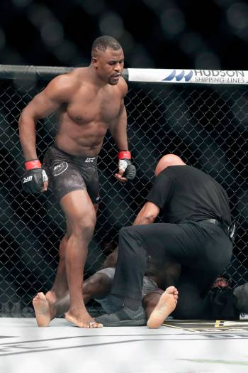Francis Ngannou, left, walks alway after knocking out Jairzinho Rozenstruck in the first round ...