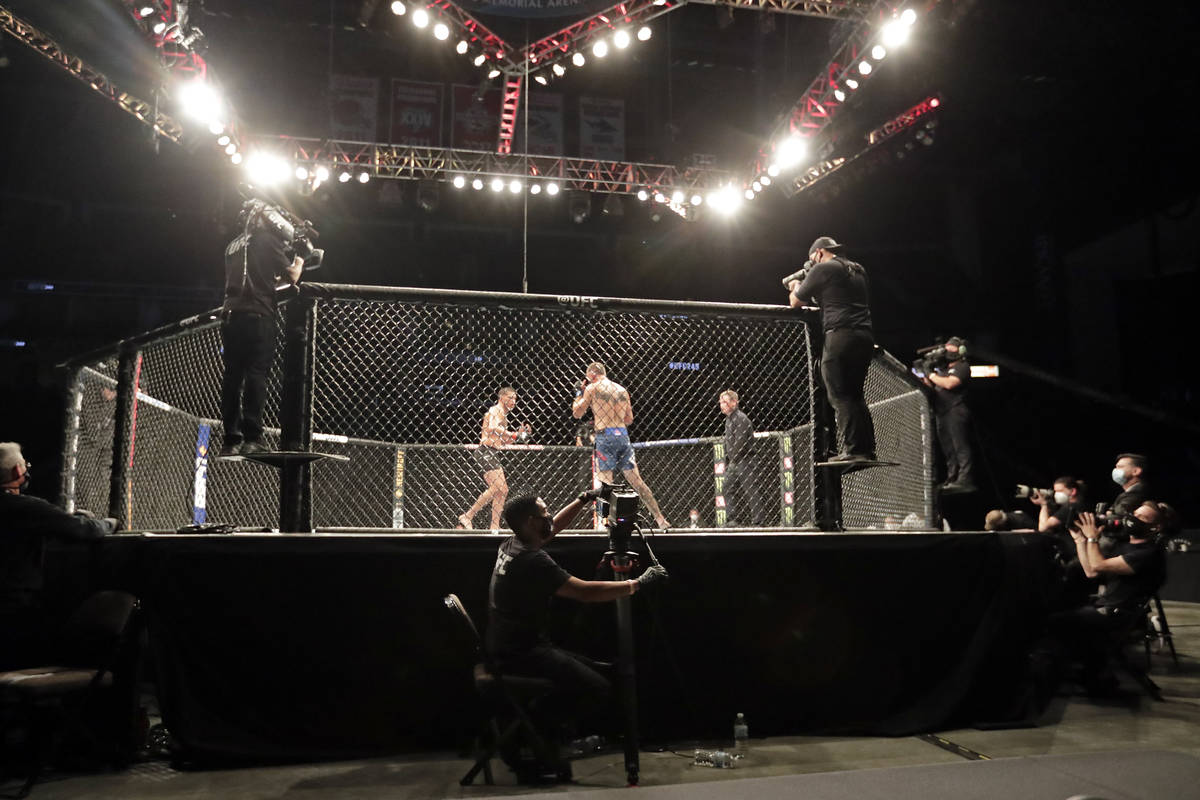 Anthony Pettis, center left, and Donald Cerrone fight during a UFC 249 mixed martial arts bout, ...