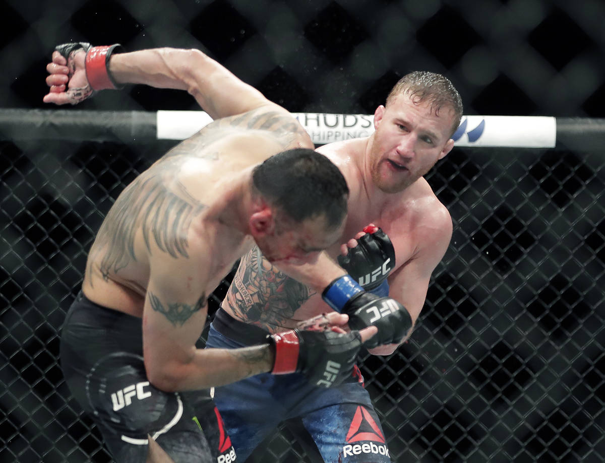 Tony Ferguson, left, falls backward after taking a punch from Justin Gaethje during a UFC 249 m ...