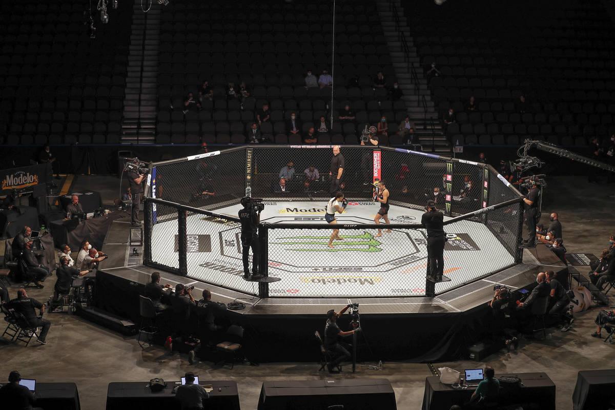 Michelle Waterson, center left, and Carla Esparza battle without spectators during a UFC 249 mi ...