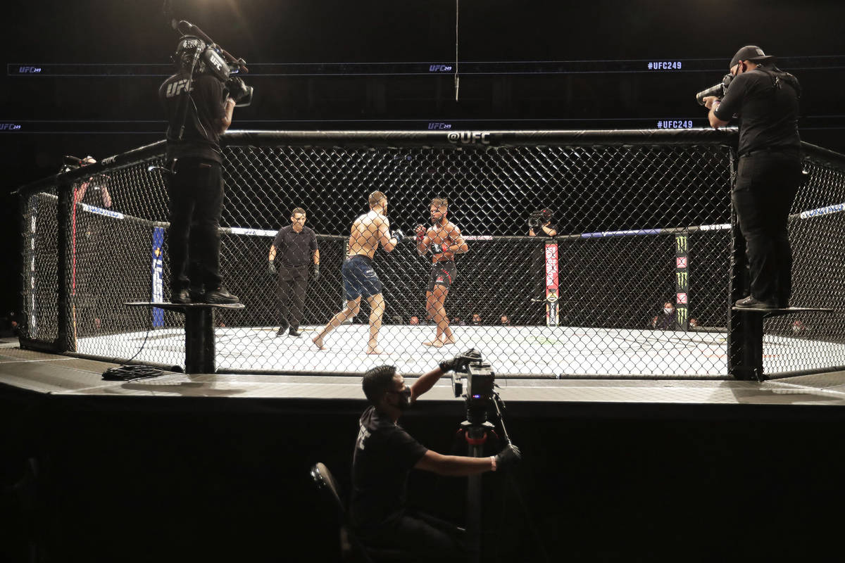 Calvin Kattar, center left, and Jeremy Stephens fight during a UFC 249 mixed martial arts bout, ...