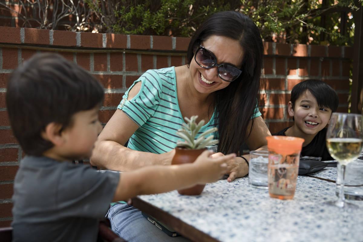 Nikki Alvarado, center, laughs with her son Joni Lum, 2, left, and her son Silas Lum, 7, right, ...