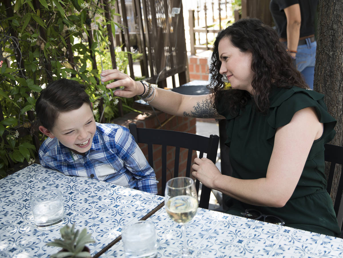 Nicole Silverman fixes the hair of her son Berkeley Brady, 8, while at brunch at 7th & Cars ...