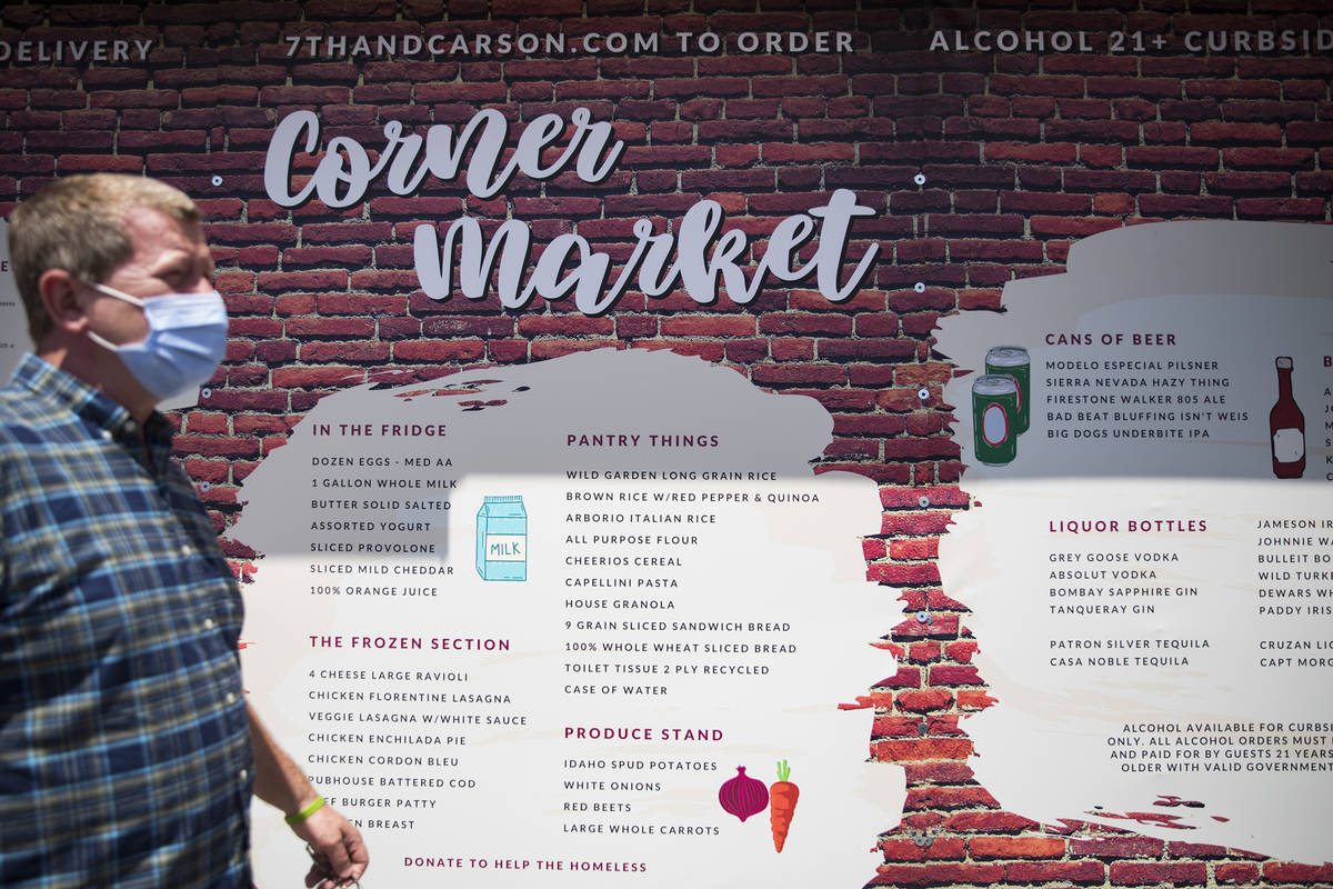 Owner Liam Dwyer walks past a giant menu at 7th & Carson in Las Vegas, Sunday, May 10, 2020 ...