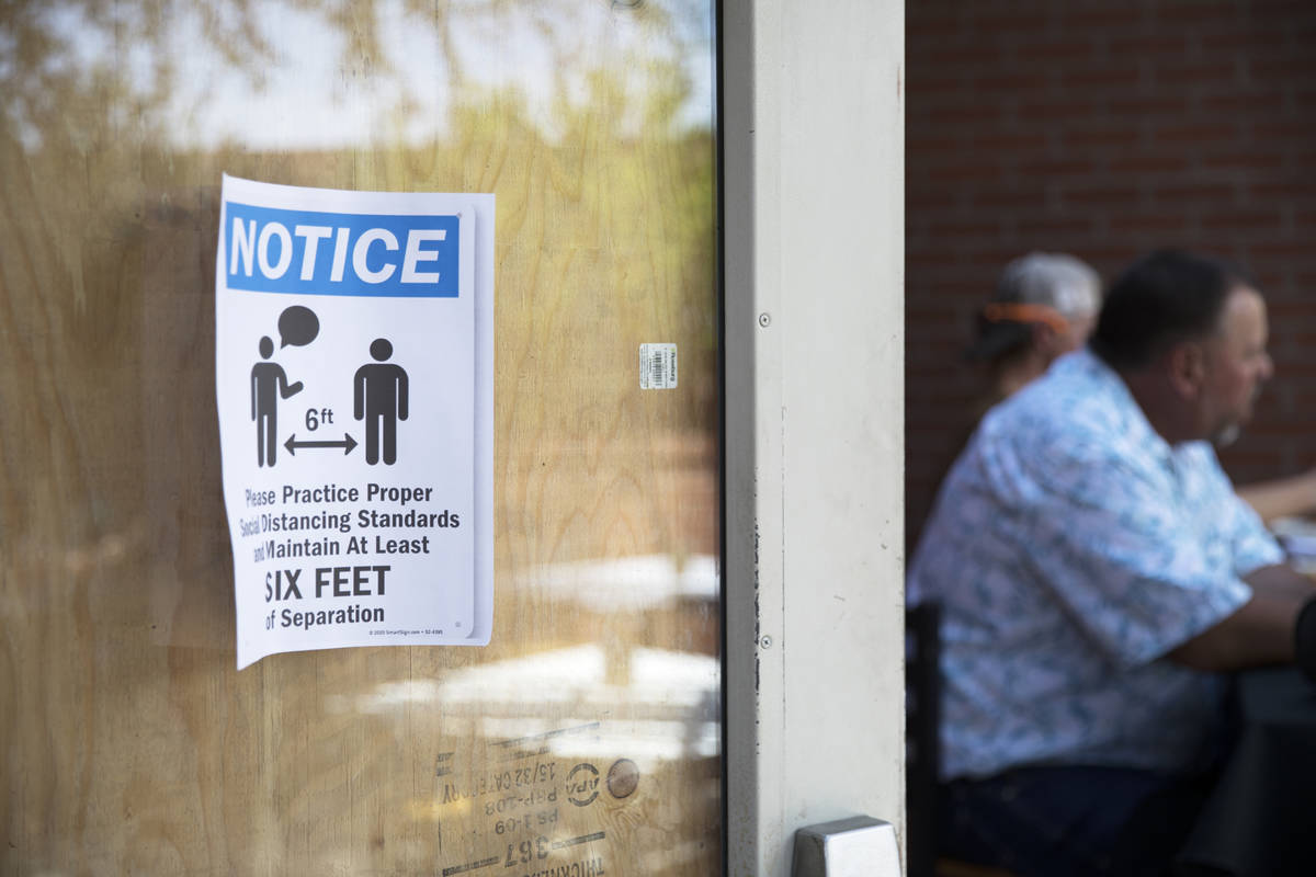 A sign to inform guests of social distancing measures on the door at 7th & Carson in Las Ve ...