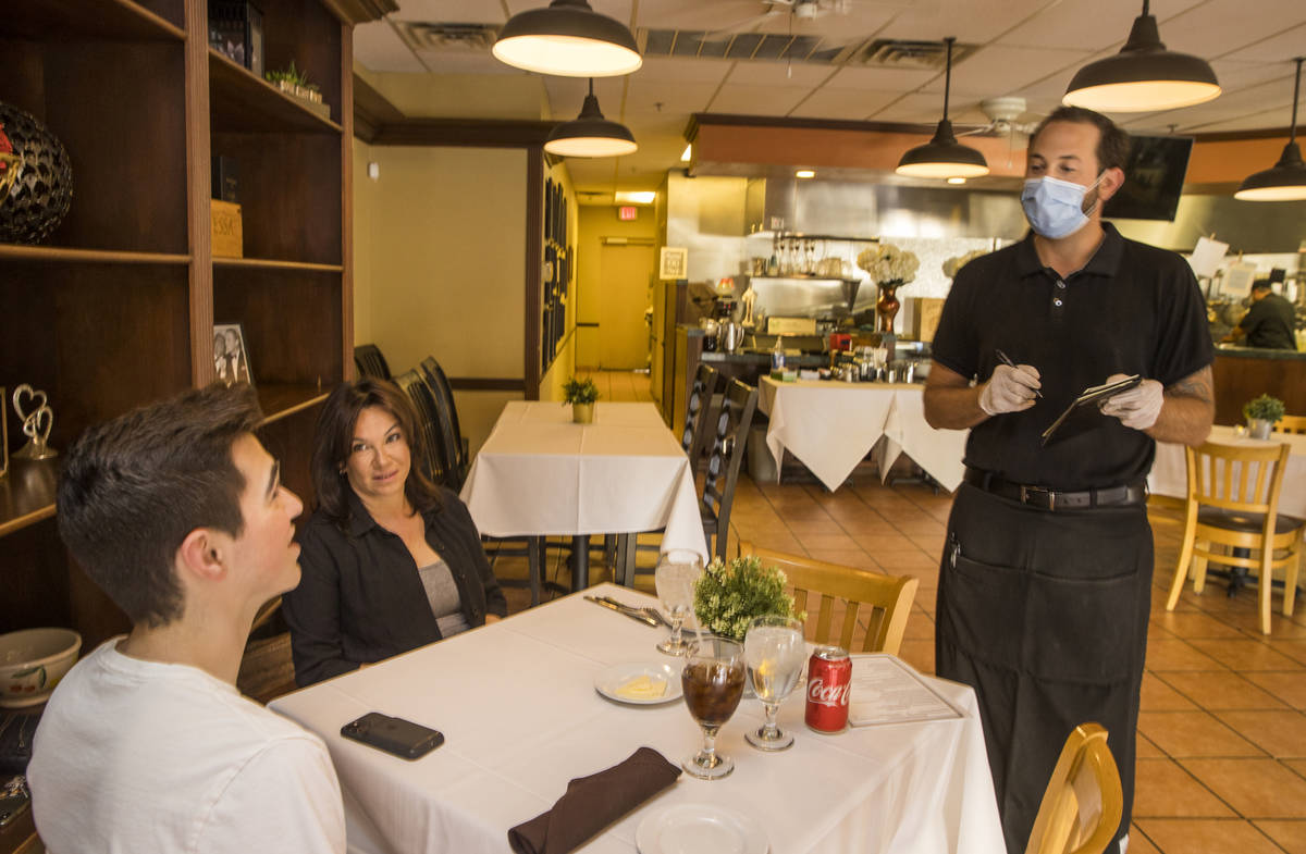 Diners Seth Andress, left, and his mother Lou have their order's taken by waiter Brennen Rudack ...