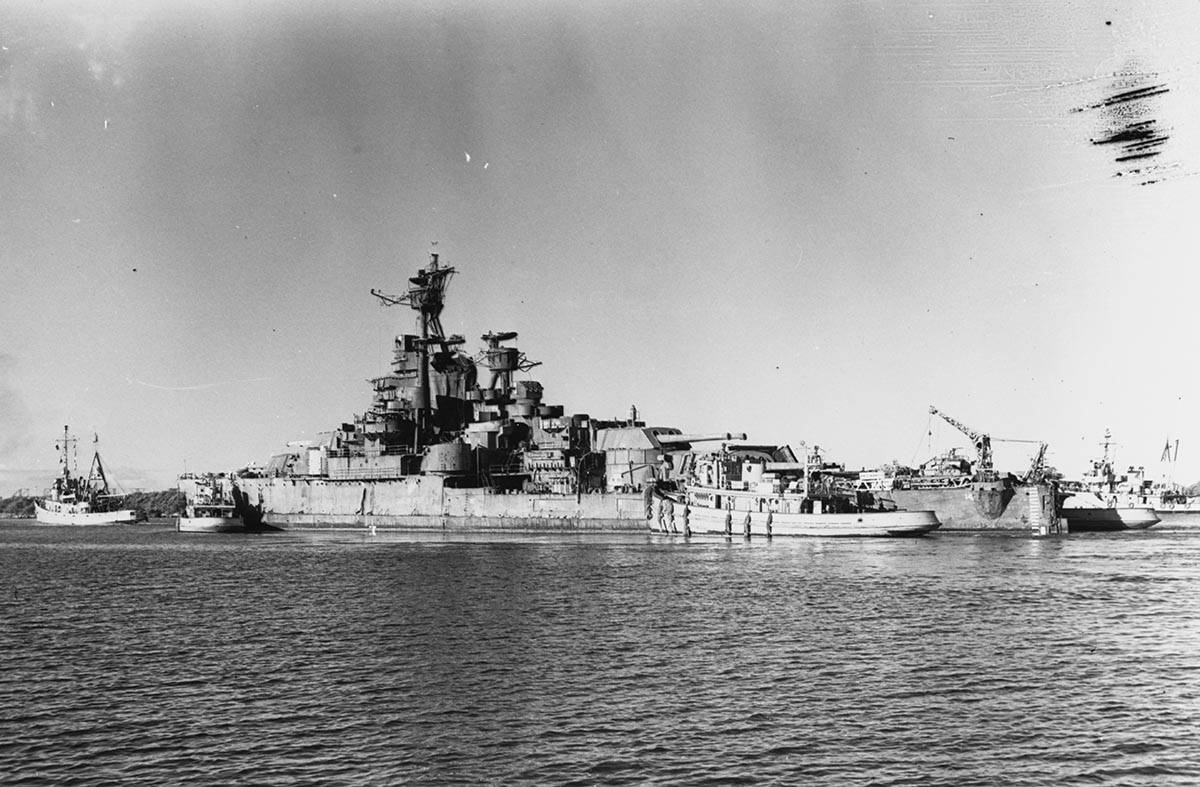 The USS Nevada's departure from Pearl Harbor under tow by the USS Jicarilla on July 26, 1948. ...
