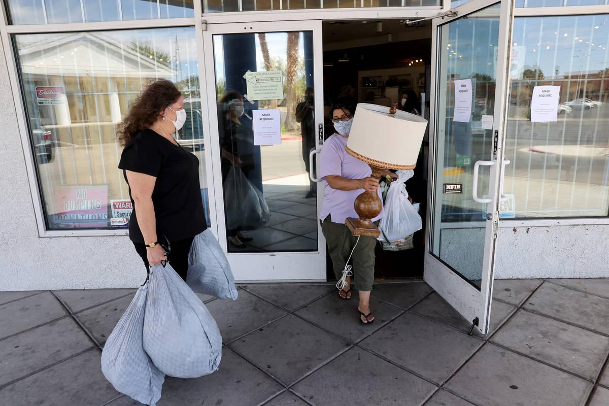 Dinosaurs & Roses Executive Director Michele Morgan, 60, loads donated items as customer Ju ...