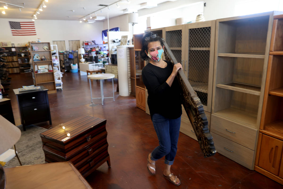 Dinosaurs & Roses customer Lucy Leija, 48, loads a mirror on the first day of reopening for ...