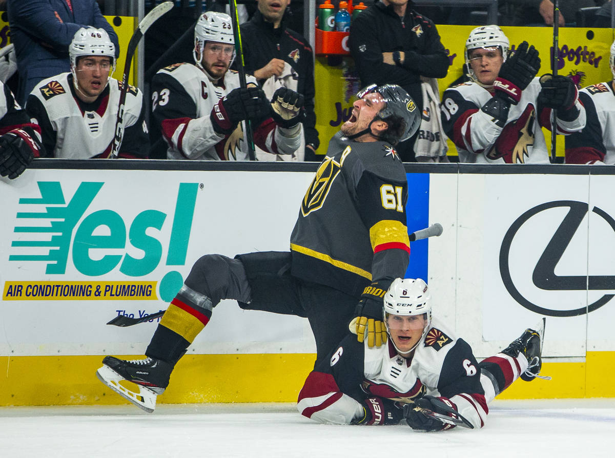 Vegas Golden Knights right wing Mark Stone (61, left) yells out in pain as Arizona Coyotes defe ...