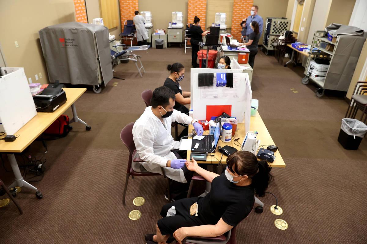 Josefina Garcia, 66, of Las Vegas prepares to donate plasma with donor care specialist Ivan Puz ...