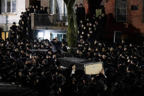 In this Dec. 11, 2019, file photo, Orthodox Jewish men carry Moshe Deutsch's casket outside a B ...