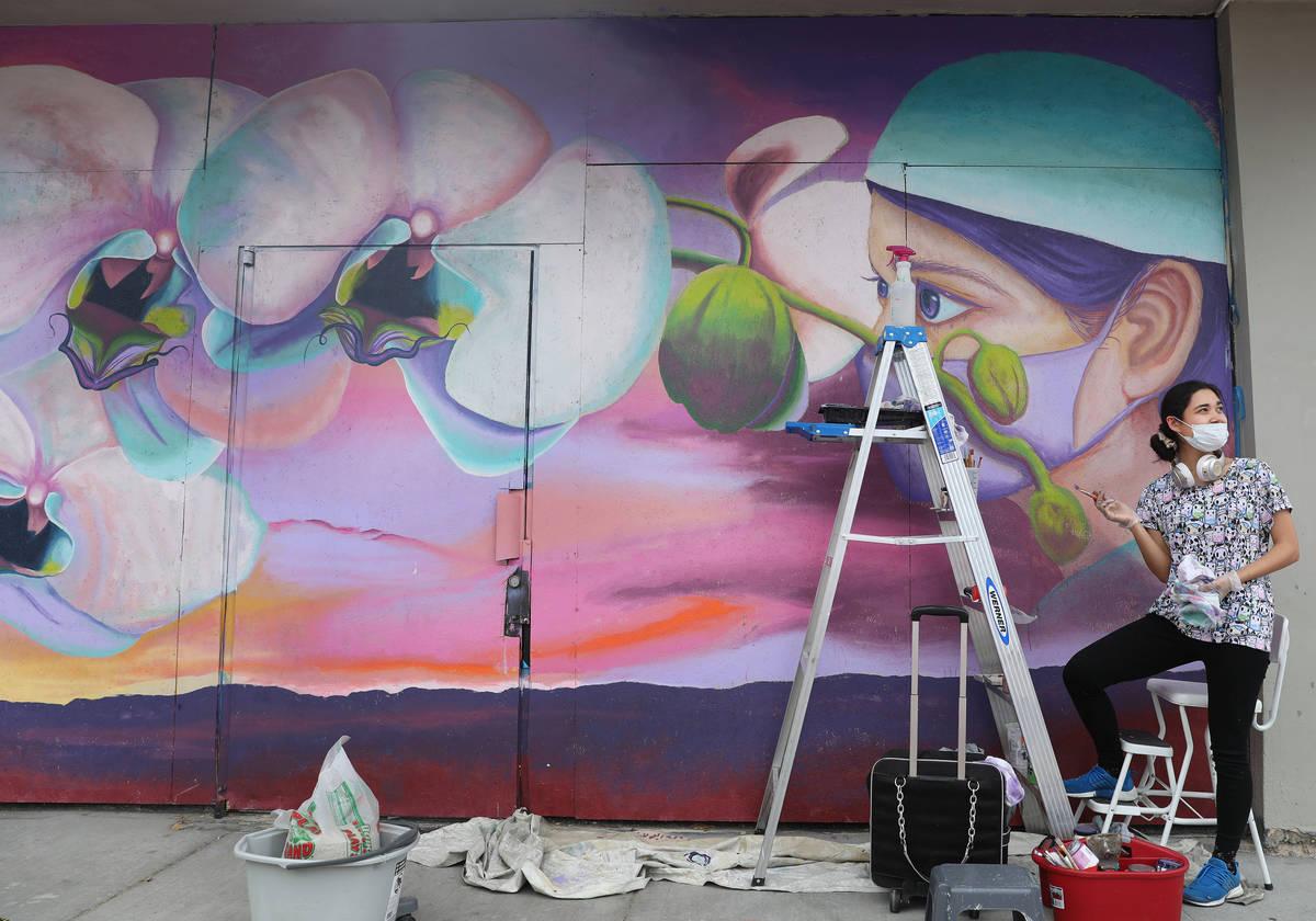 Chelsea Rust, muralist and staff of Priscilla Fowler Fine Art, paints a mural of a Las Vegas Va ...