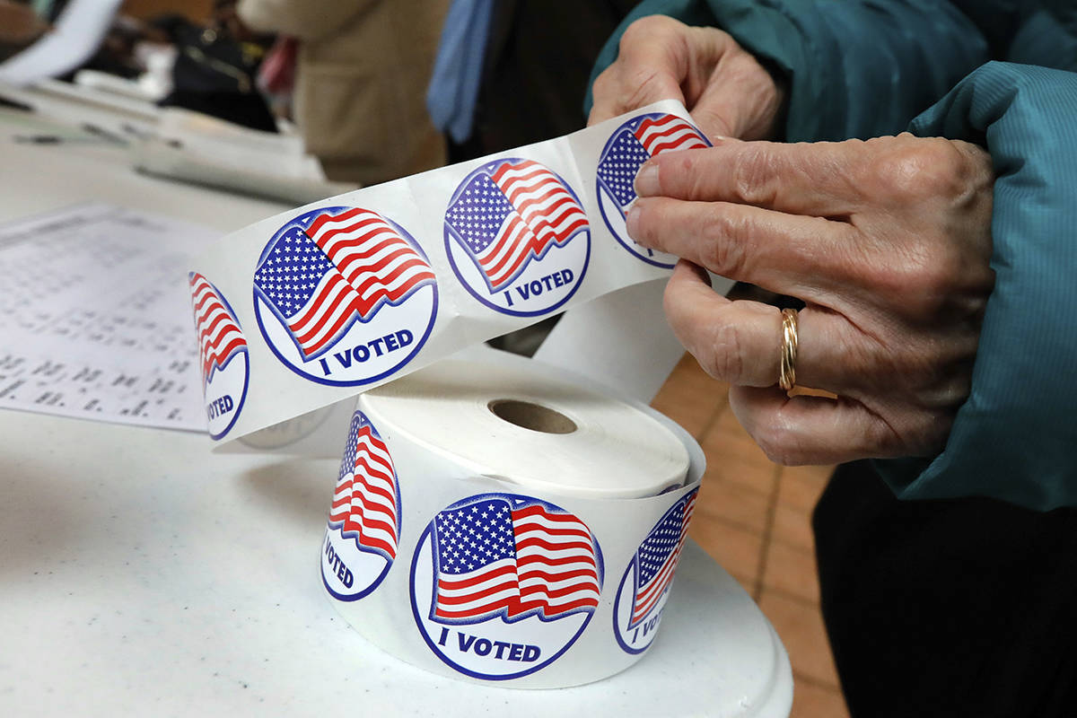"""FILE - In this Tuesday, Nov. 6, 2018 file photo, a voter peels off an """"I Voted"""" sticker after c ..."""