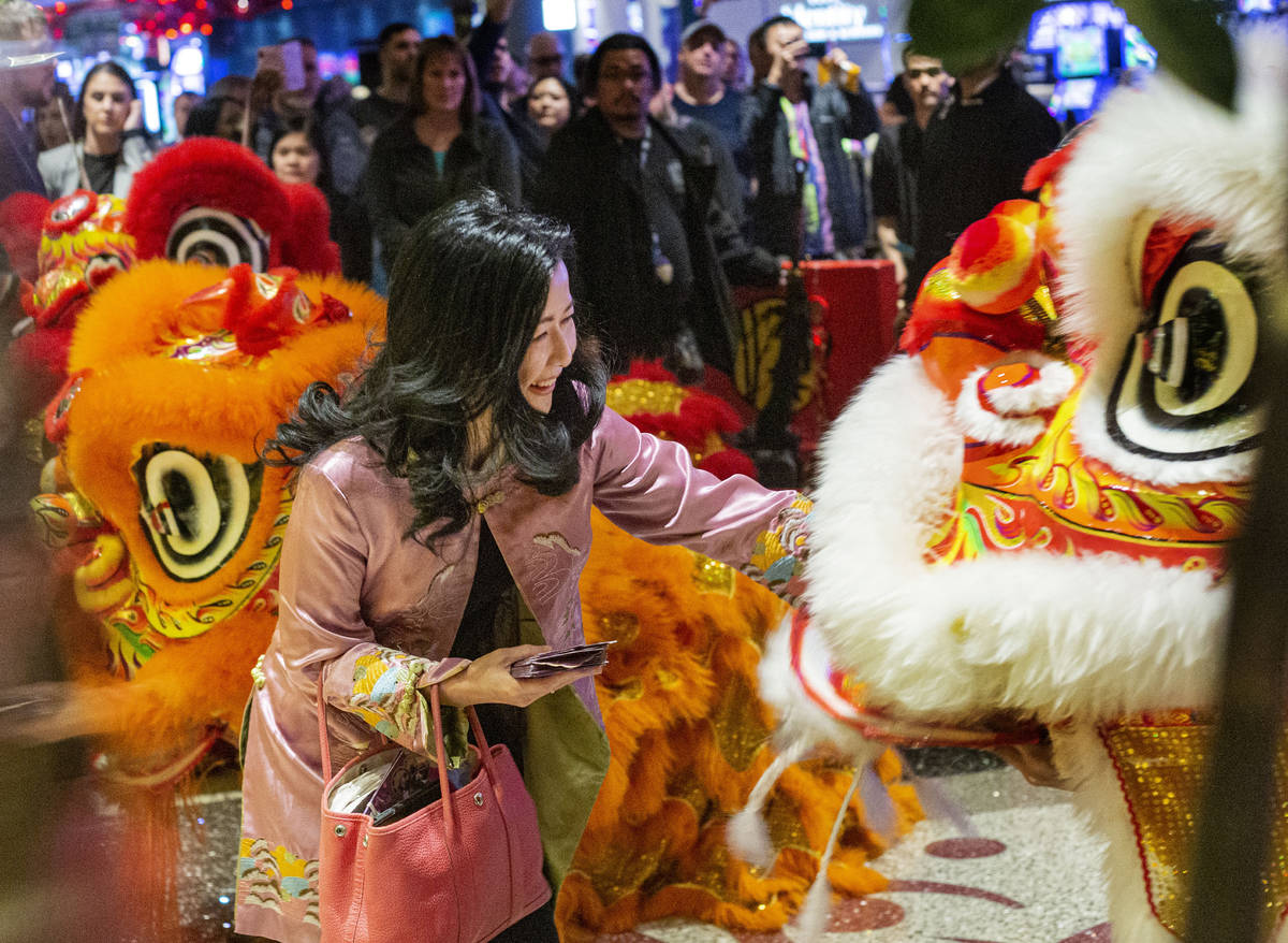 Siew-Lee Yee, president of Far Marketing, feeds a lion during ceremonial dance performance in h ...
