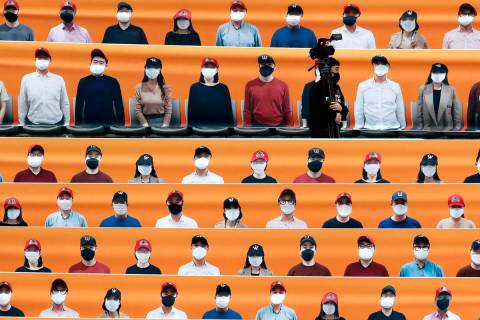 A TV cameraman walks through the spectators' seating which are covered with pictures of fans, b ...