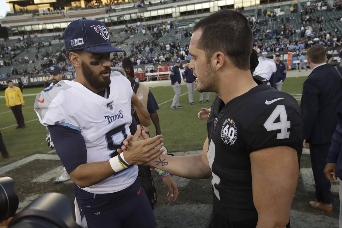 Tennessee Titans quarterback Marcus Mariota, left, greets Oakland Raiders quarterback Derek Car ...