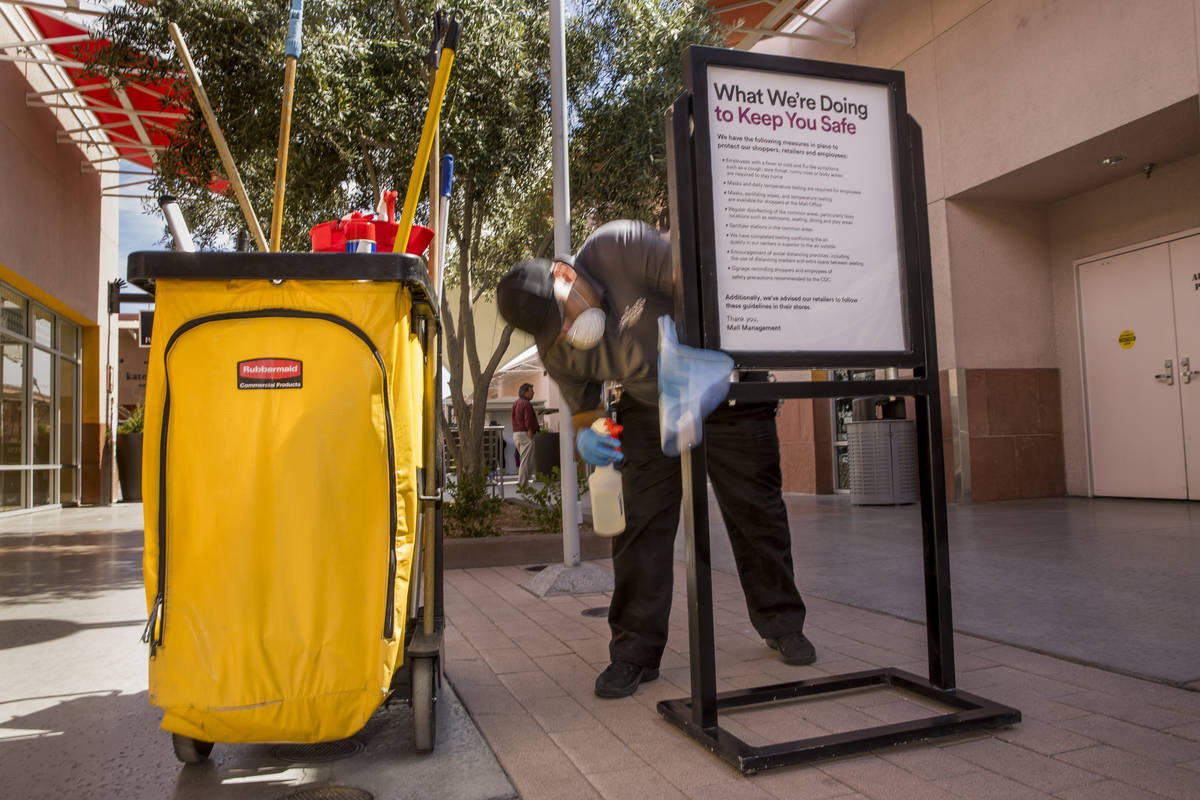 Ivan Leybe sanitizes one of the many customer information signs now installed throughout the La ...