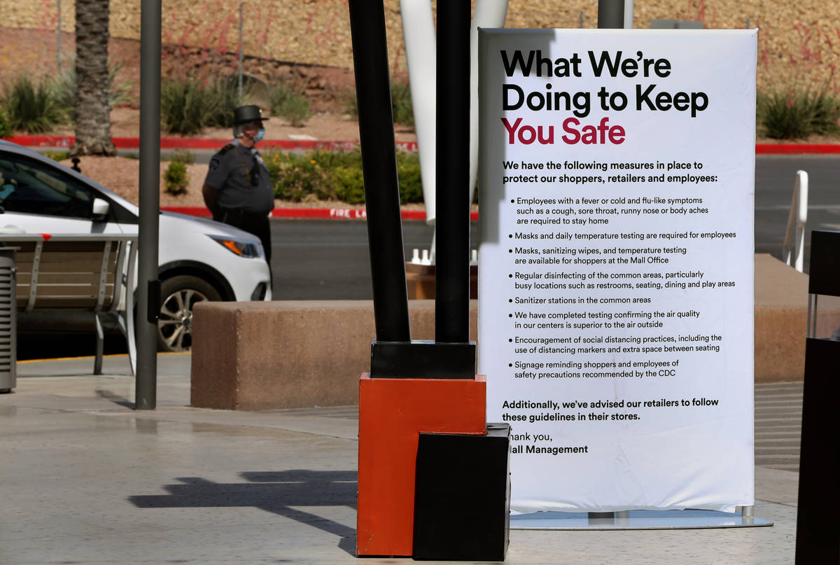 A security guard stands duty past one of the many customer information signs now installed thro ...