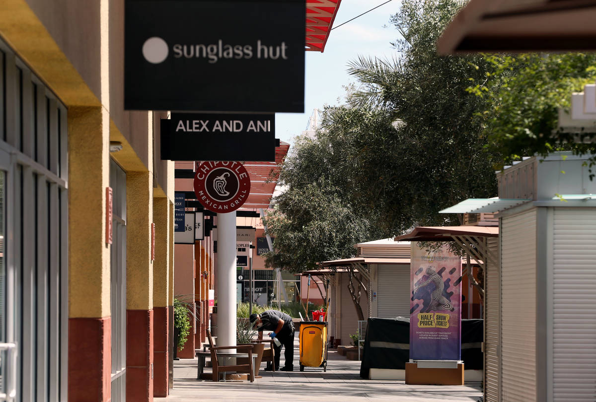 Ivan Leybe sanitizes customer areas within the Las Vegas North Premium Outlets as seen during a ...