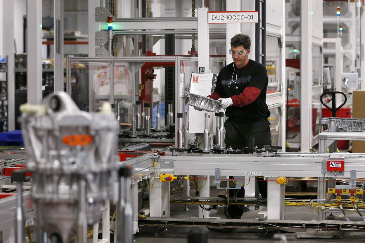 An employee assembles a drive unit at the Tesla Gigafactory, east of Reno. (Cathleen Allison/La ...