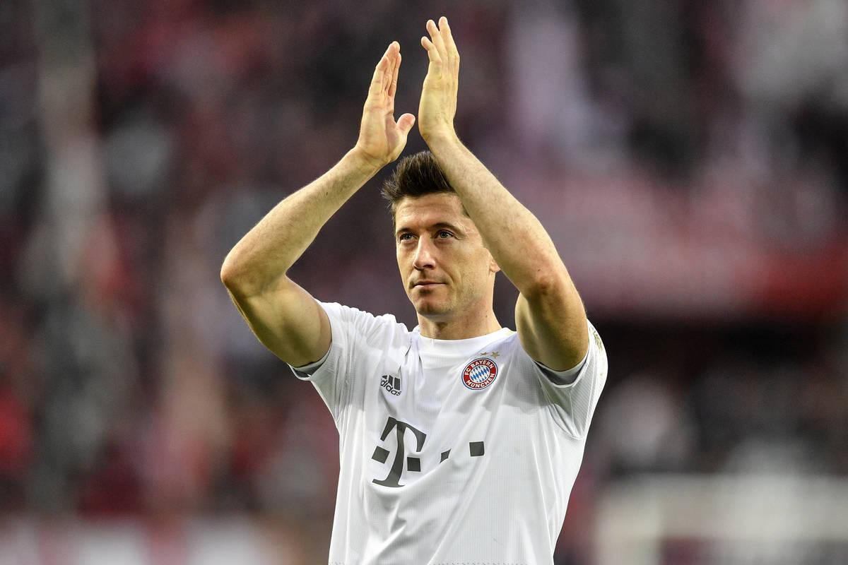 In this Sunday, Feb. 16, 2020 file photo, Bayern's Robert Lewandowski celebrates with supporter ...