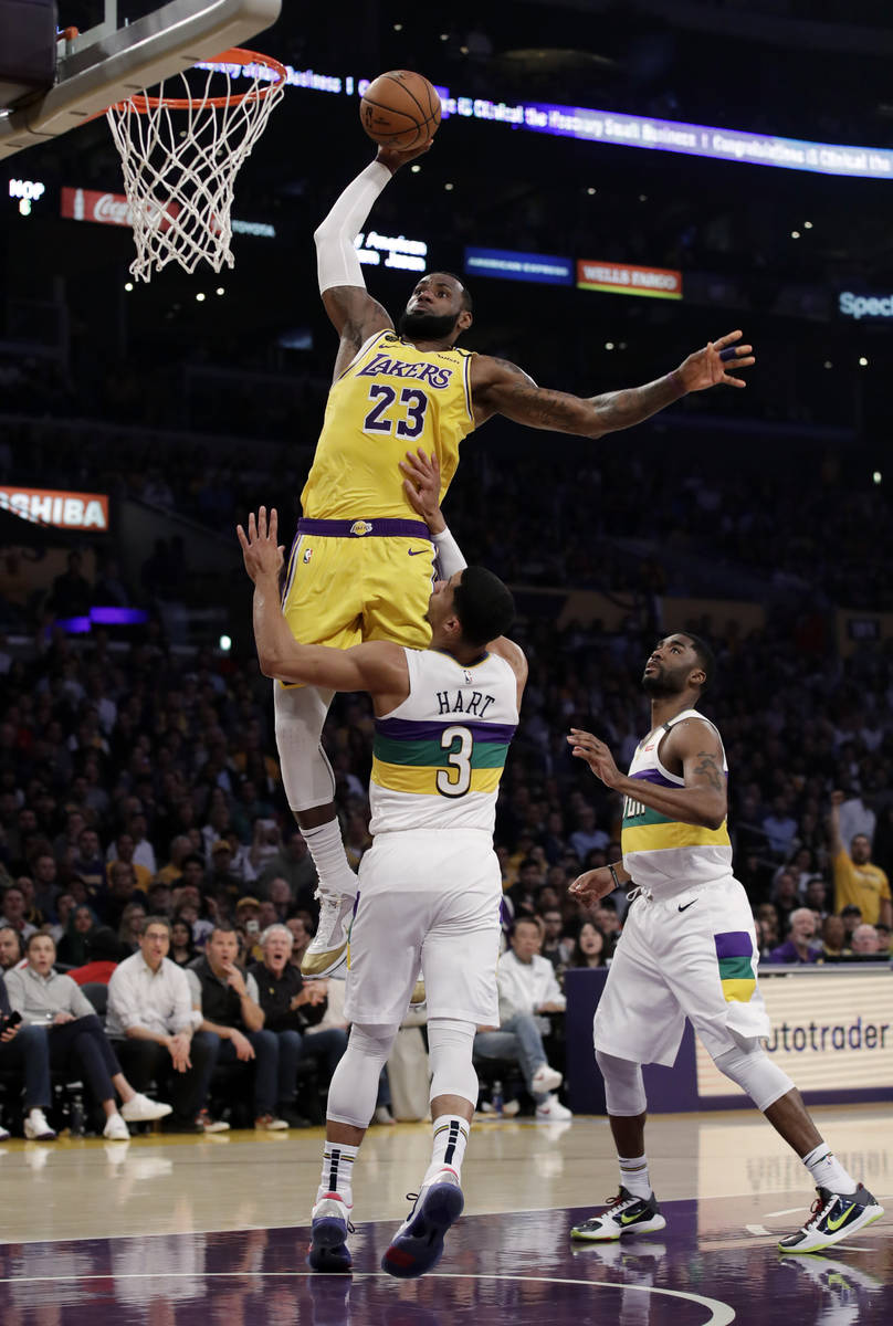 Los Angeles Lakers forward LeBron James (23) dunks over New Orleans Pelicans' Josh Hart (3) dur ...
