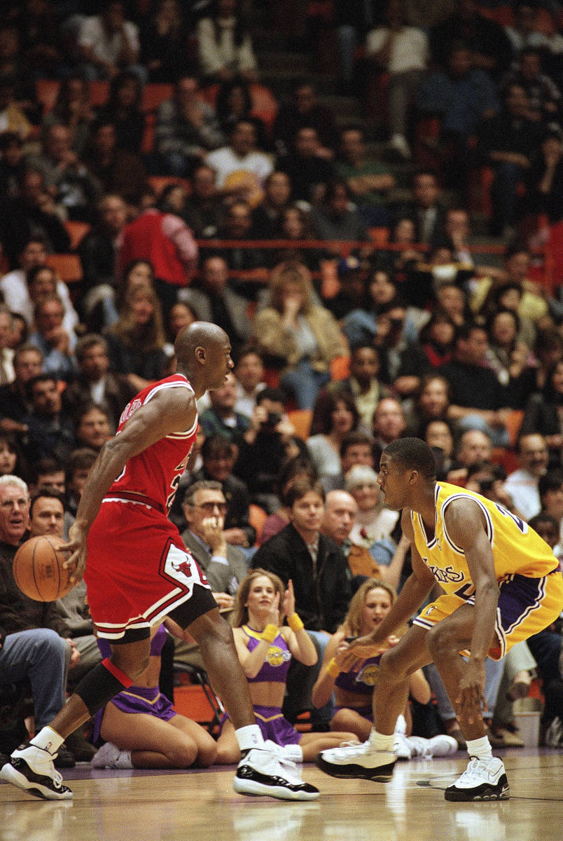 The Chicago Bulls' Michael Jordan, left, palms the ball as the Los Angeles Lakers? Eddie Jones ...