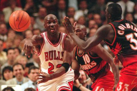 Chicago Bulls' Michael Jordan passes off around Atlanta Hawks' Mookie Blaylock (10) and Tyrone ...