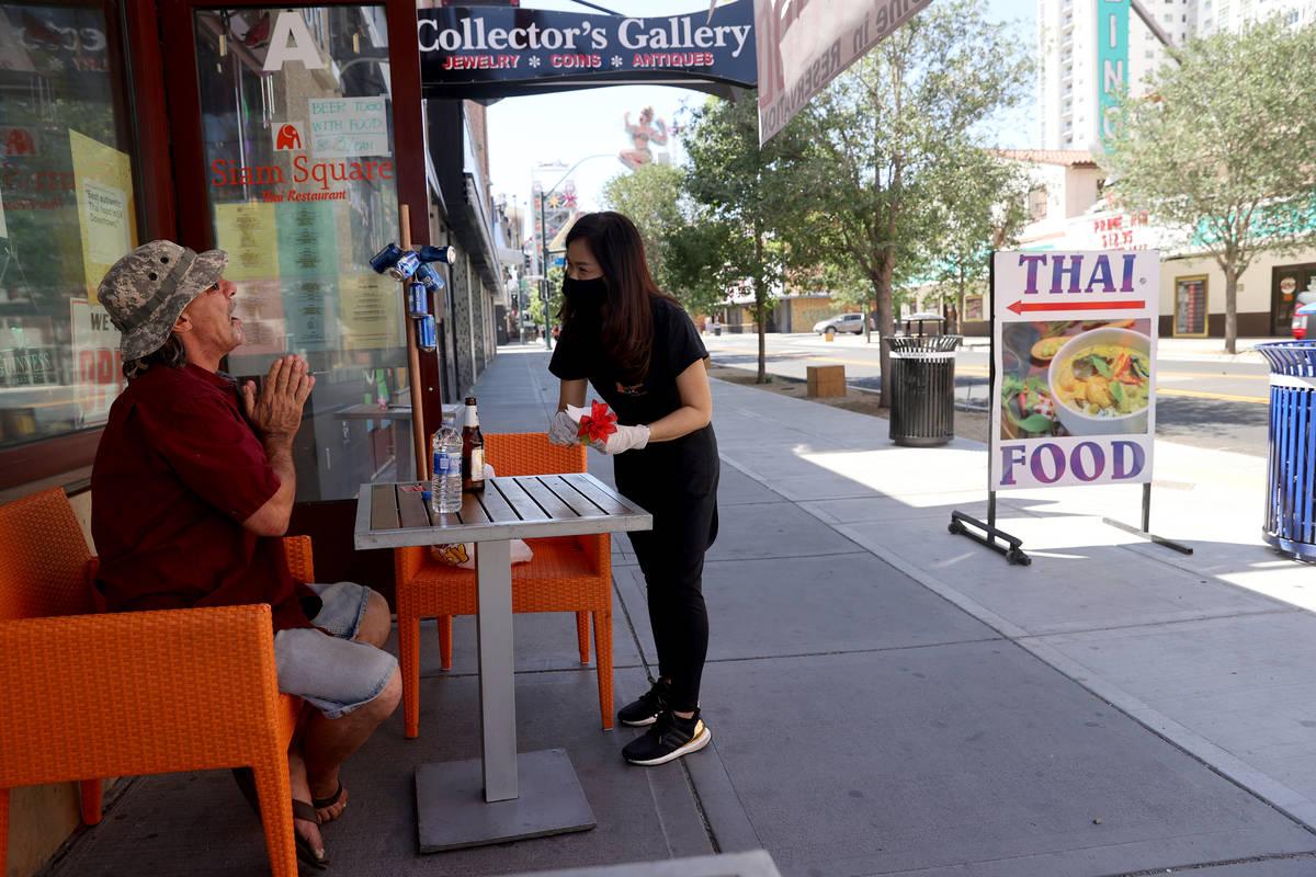 Jenny Prapasanobol, a server Siam Square on East Fremont Street in downtown Las Vegas, helps Da ...
