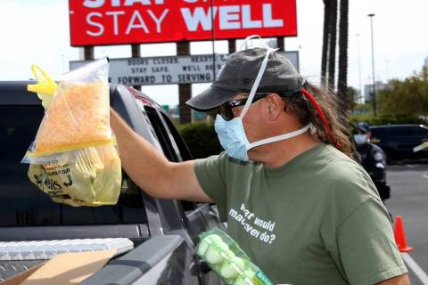 Brian Fisher, 53, of Las Vegas helps distribute food at Palace Station in Las Vegas Thursday, A ...