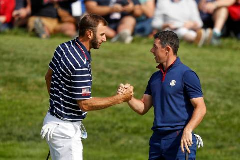 In this Sept. 28, 2018, file photo, Dustin Johnson left, and Rory McIlroy shake hands on 16th g ...