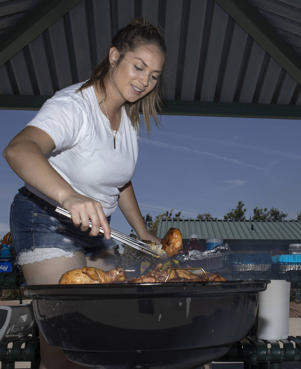 Anna Sewell grills barbecue chicken to celebrate her friend's birthday at Pioneer Park on Satur ...
