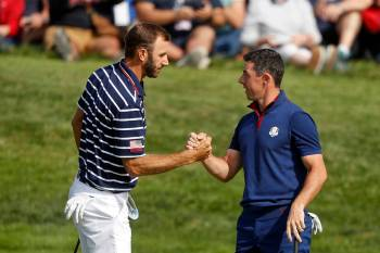 FILE - In this Sept. 28, 2018, file photo, Dustin Johnson left, and Rory McIlroy shake hands on ...