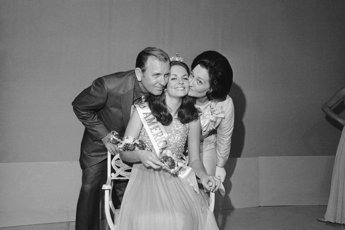 Miss America of 1971, 21-year-old Phyllis George, of Denton, Texas, is embraced by her parents, ...
