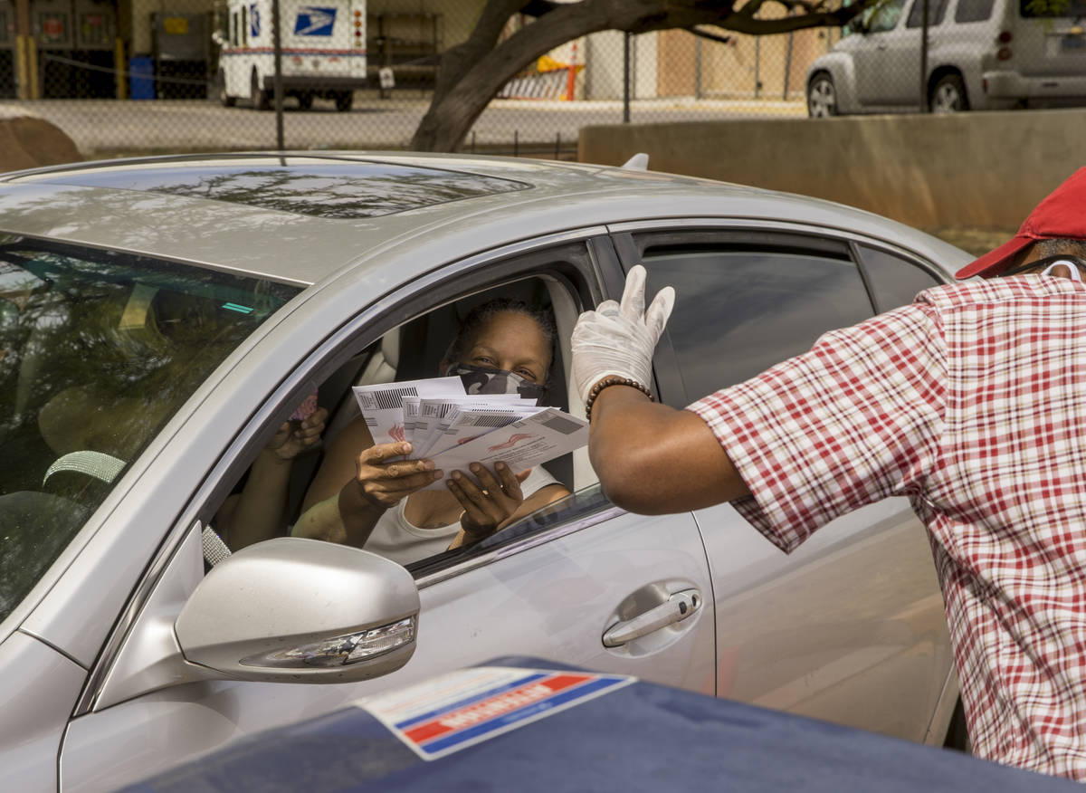 A driver hands over completed ballots to Clark County Commission Vice Chairman Lawrence Weekly ...