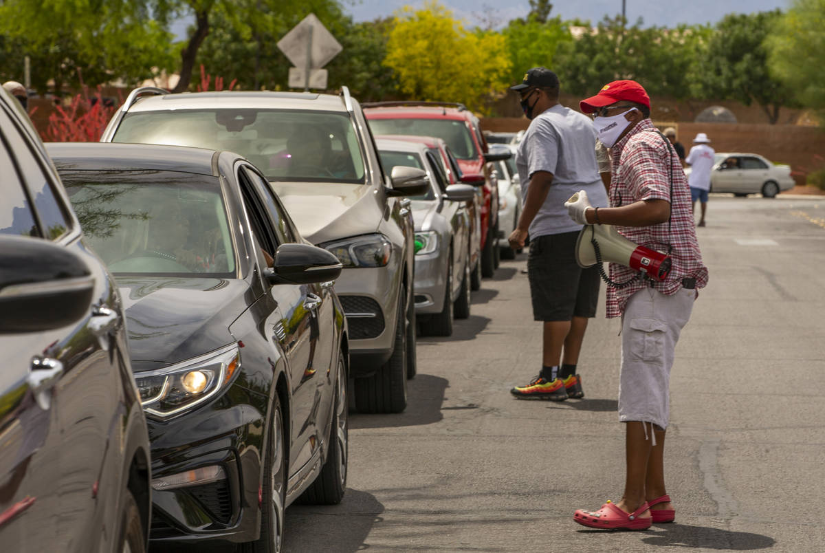 Clark County Commission Vice Chairman Lawrence Weekly chats up drivers waiting in line while du ...