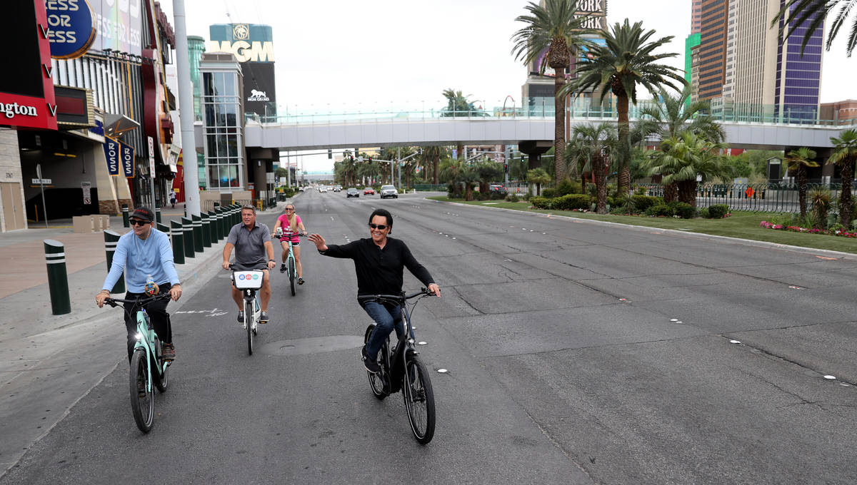 Mr. Las Vegas Wayne Newton, right, rides a bicycle on the Strip in Las Vegas with, from left, L ...