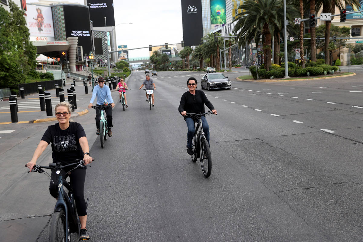 Mr. Las Vegas Wayne Newton, right, rides a bicycle on the Strip in Las Vegas with, from left, w ...