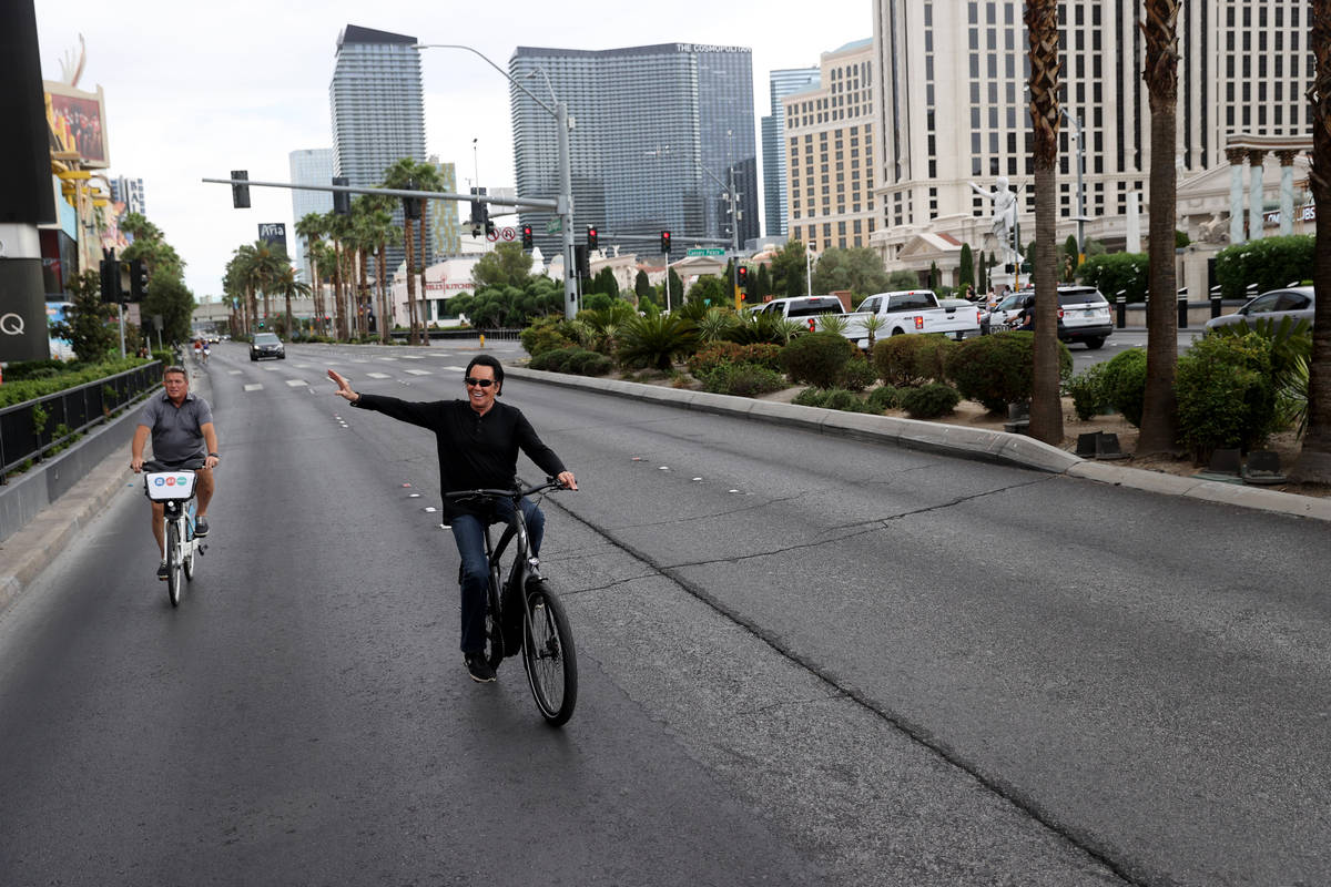 Mr. Las Vegas Wayne Newton, right, waves to fans while riding a bicycle on the Strip in Las Veg ...