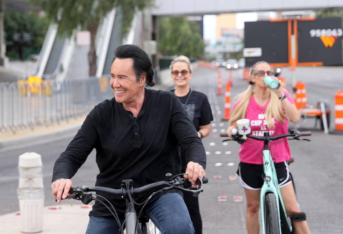 Mr. Las Vegas Wayne Newton, left, rides a bicycle on the Strip in Las Vegas with wife Kathleen ...